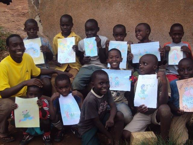 Happy and Children from Uganda holding their drawings